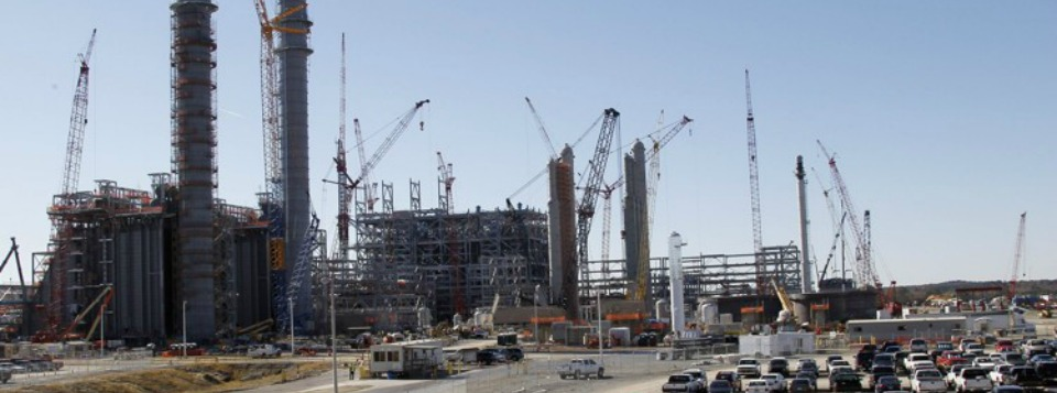 """Workers vehicles fill parking lots at Mississippi Power's Kemper County energy facility near DeKalb, Miss., in this 2012 photo. Delays and cost overruns at the """"clean coal"""" plant have weighed on Southern Co.'s bottom line. (AP Photo/Rogelio V. Solis, File)"""